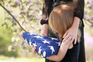 Daughter holding a parent's folded American flag with a woman's arms wrapped around her.